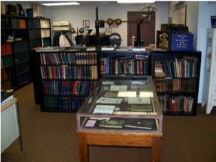 """View toward book stacks and """"classroom"""" area. Glass display case contains books published in 1896."""